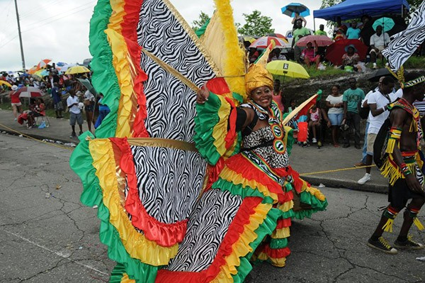 a woman dressed in colorful carnival costume and the audience at Crop Over festival in Barbados