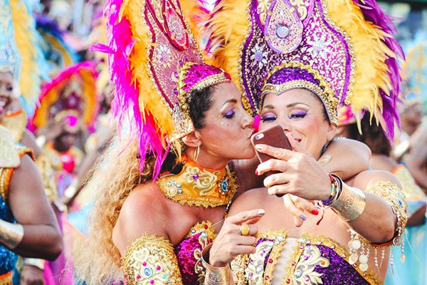 two women taking a selfie dressed in colorful Crop Over carnival outfit