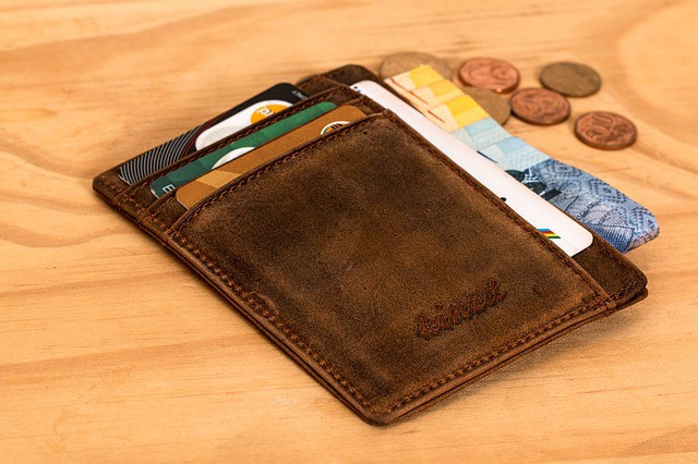wallet with money and credit cards on a table