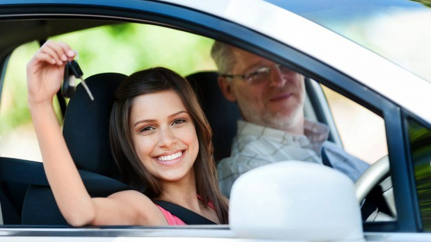woman with the car key in her hand in a rental car with a professional driver