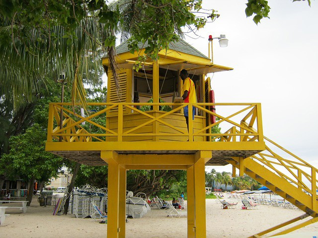 yellow wooden watch house on Barbados beach