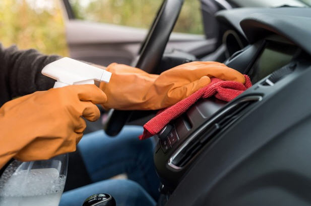 worker_cleaning_disinfect_interior_of_hire_vehicle